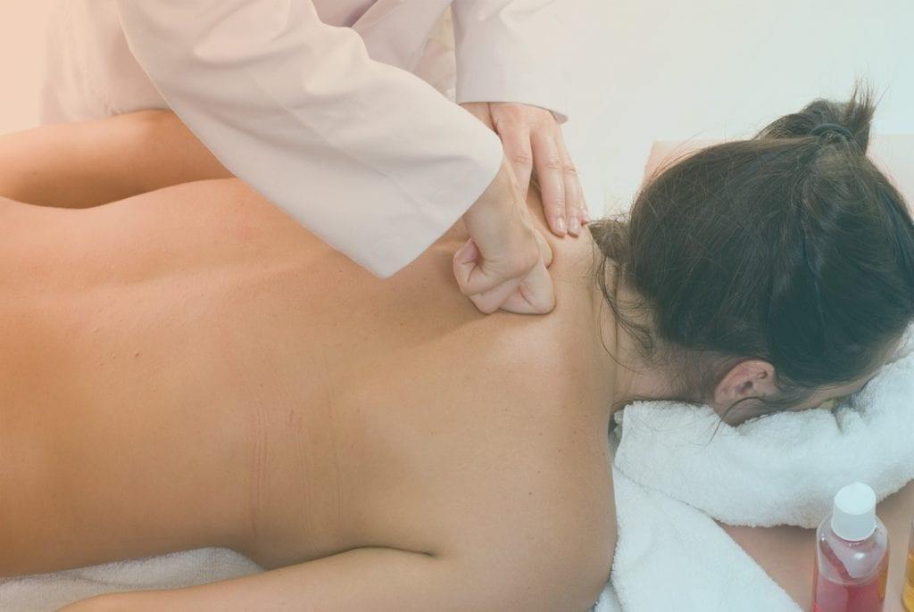 Massage therapist massaging female patients upper back.