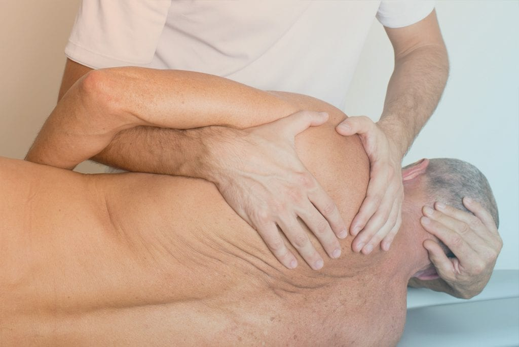 Chiropractor adjusting older male patients shoulder.