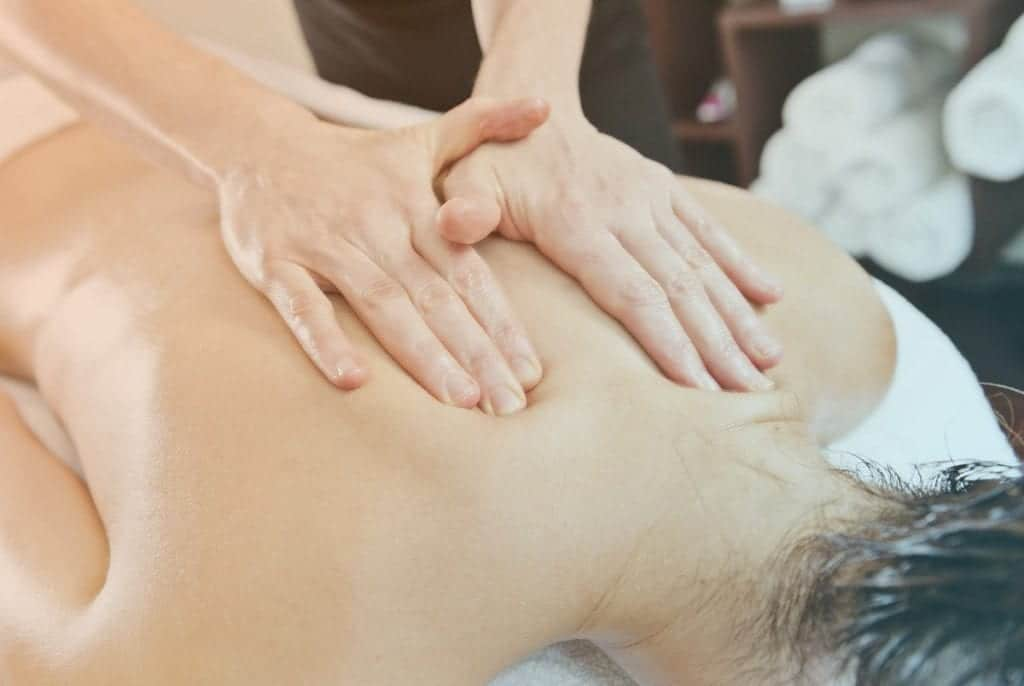 Massage therapist giving a massage to a female patient.