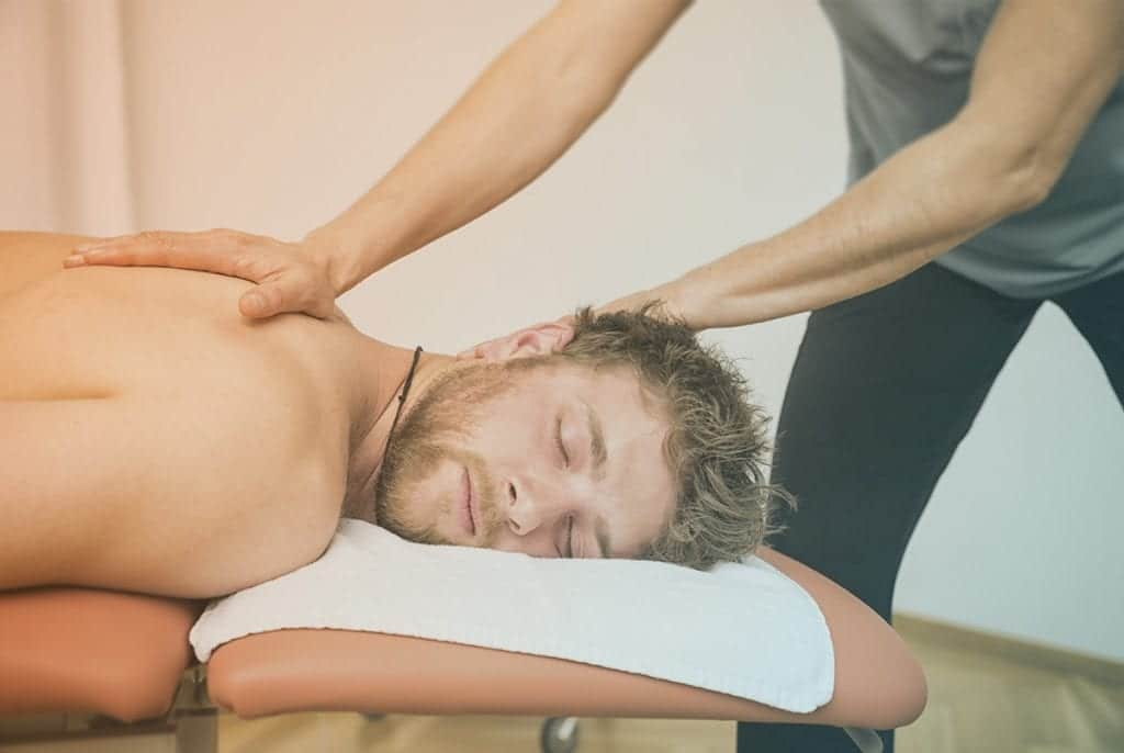 Massage therapist massaging young male upper back.