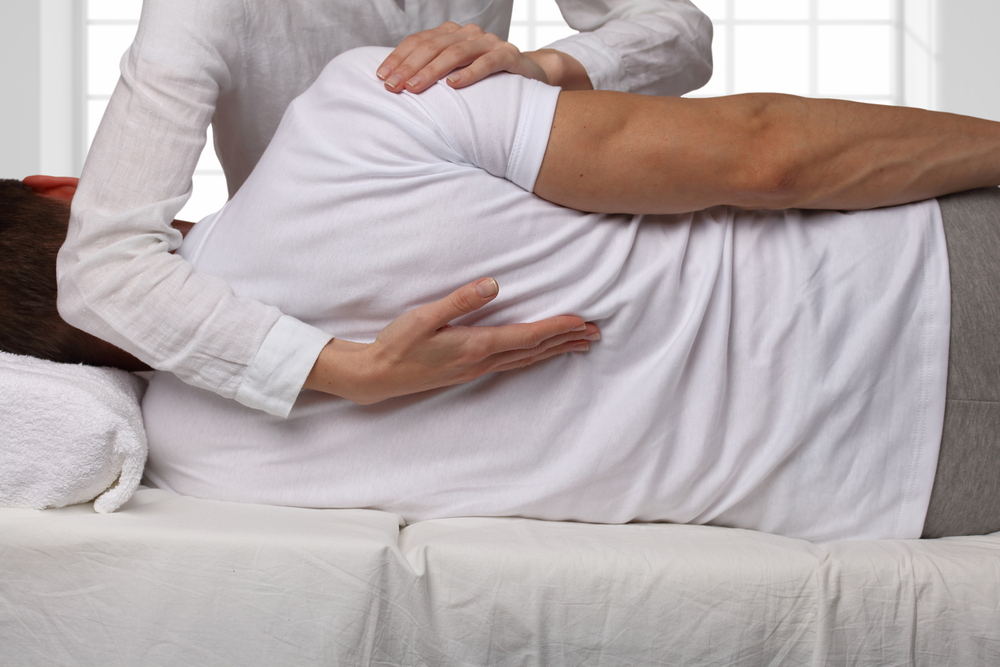 chiropractor adjusting male patient upper back