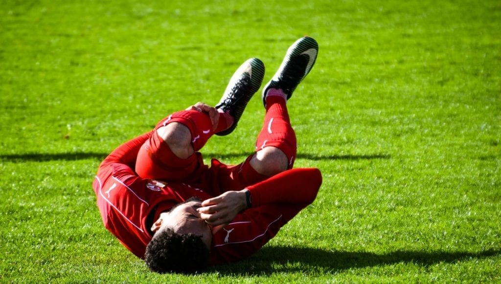 Injured soccer player crouching in the playing field.