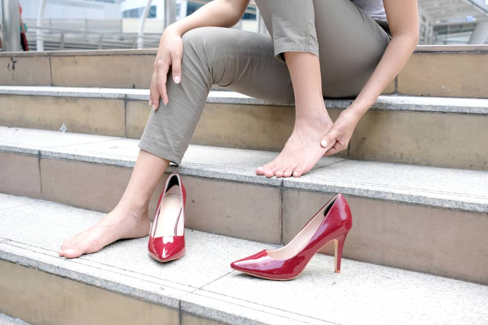 Woman with Foot Pain treatment needed holds her foot on stairs.