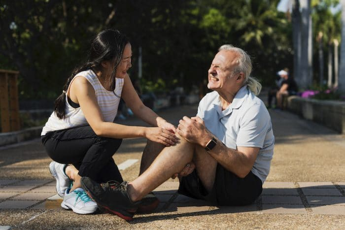 Elderly man holding his knee due too knee pain from running.