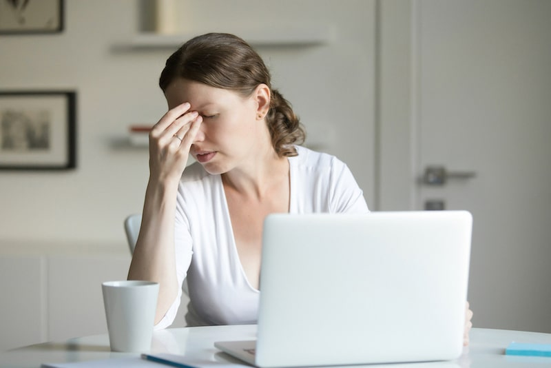 woman on her laptop having a headache