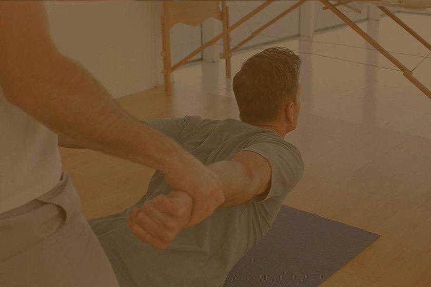 Chiropractor adjusting male patient upper back