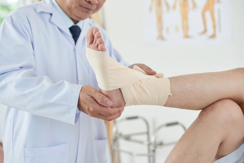 chiropractor wrapping patients ankle with bandage
