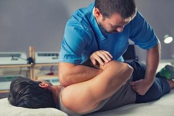Chiropractor adjusting patients back.