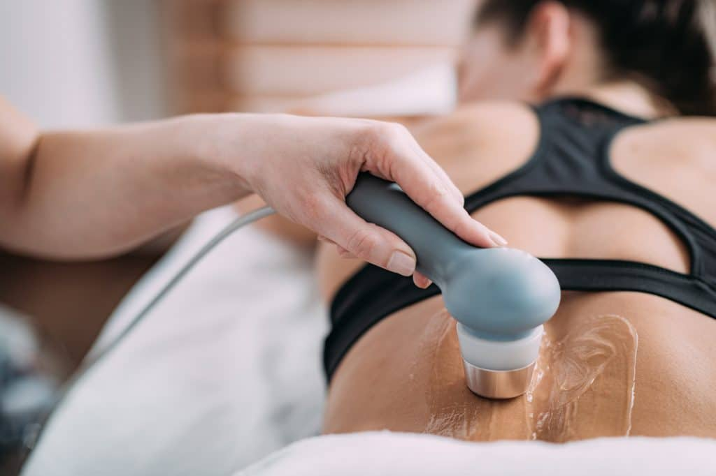 Chiropractor examining a patient with Neuromuscular ultrasound equipment