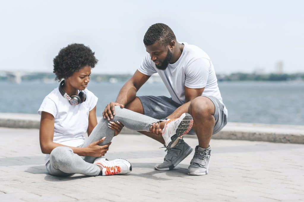 Man helping a woman on the road suffering from ankle pain.