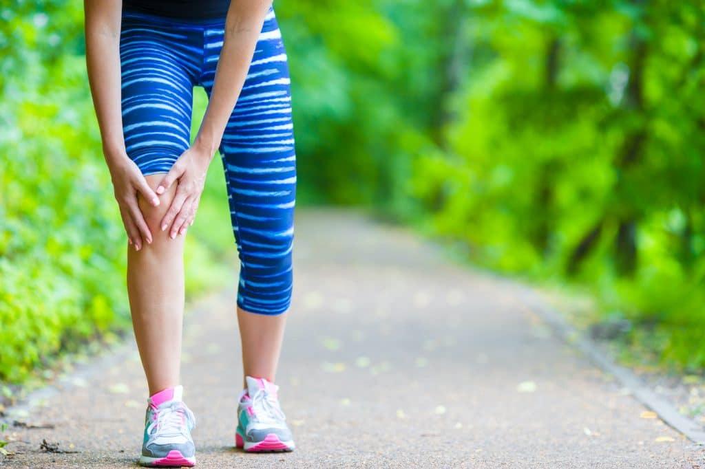 Female runner holding her knee due to a sprain.