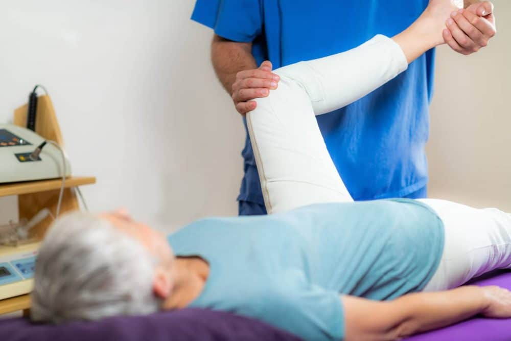 elderly woman having her knee leg stretched by a chiropractor