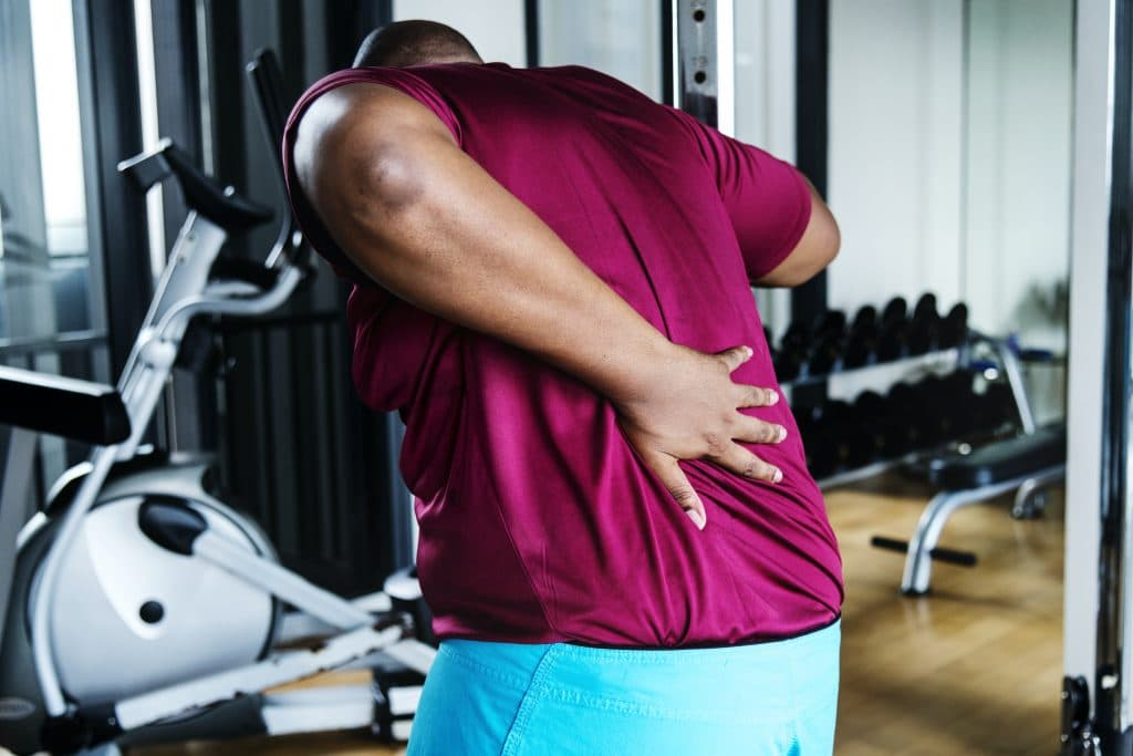 Young man holding his back due to pain in the gym