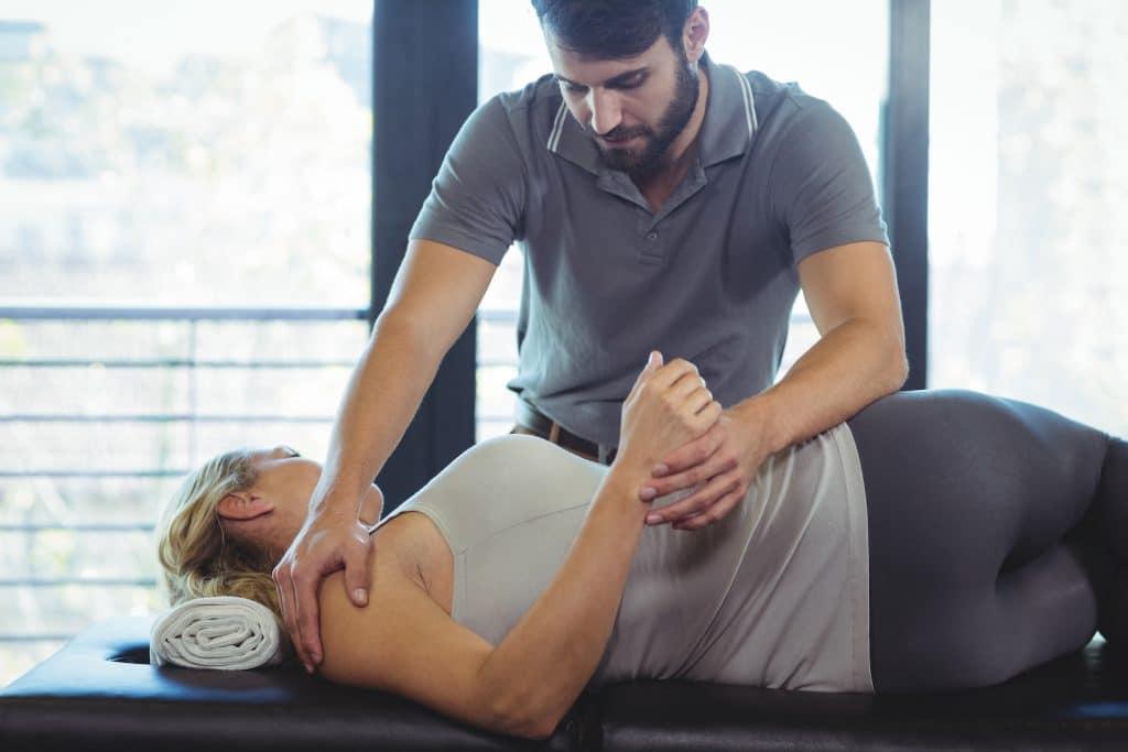 Chiropractor adjusting female patient's frozen shoulder