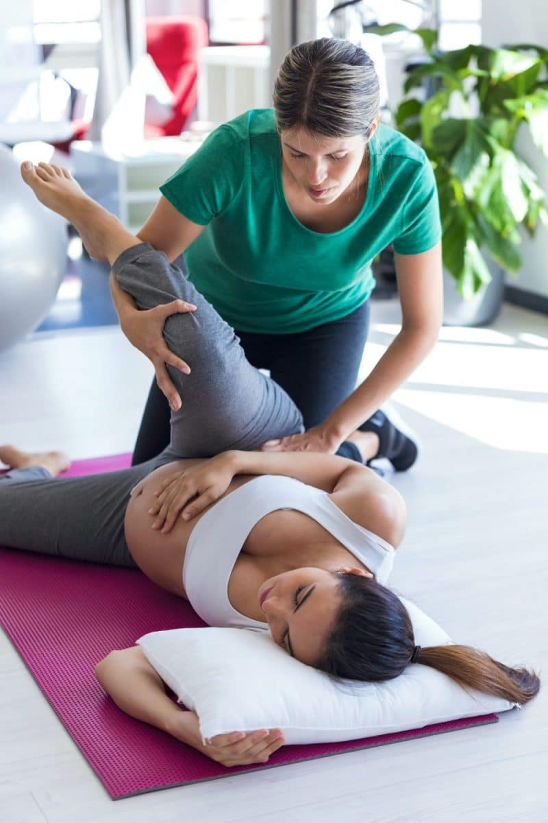 female chiropractor adjusting a pregnant woman