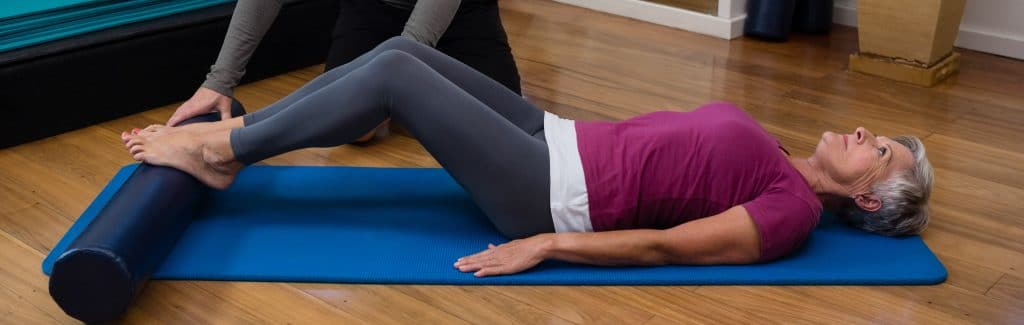 Patient stretching her hips with the help of a physical therapist.