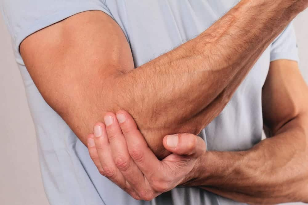 Muscular man holding his elbow because of pain.