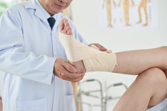 Doctor treating a patient with foot pain in newport.