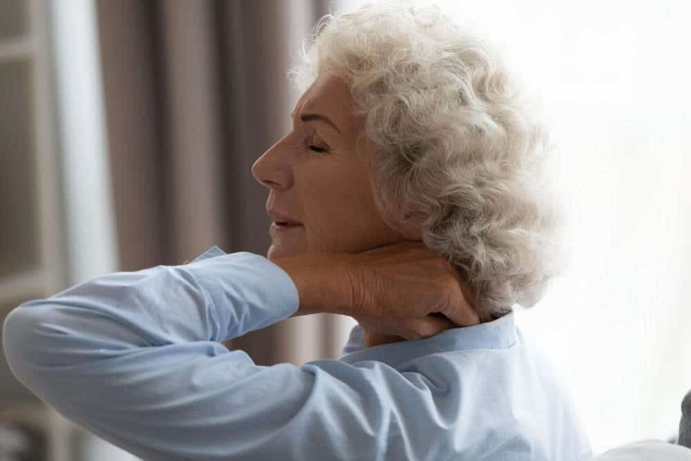 Elderly woman getting up from bed and experiencing numbness and tingling sensations